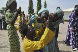 FILE - Family members celebrate as they embrace a relative, one of the released kidnapped schoolgirls, in Abuja, Nigeria, May 20, 2017. The 82 Nigerian schoolgirls recently released after more than three years in Boko Haram captivity reunited with their families.