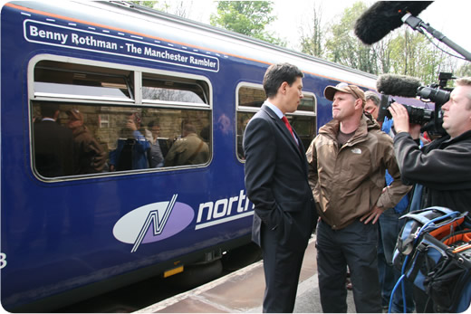 David Miliband with camera crew beside the named train