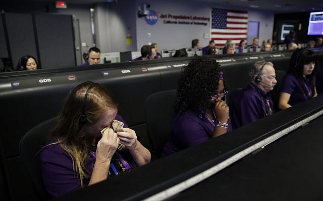 Engineer Nancy Vandermay, left, wipes her tears in mission control at NASA's Jet Propulsion Laboratory after confirmation of Cassini's demise Friday, Sept. 15, 2017, in Pasadena , Calif. (Jae C. Hong, Pool/AP)