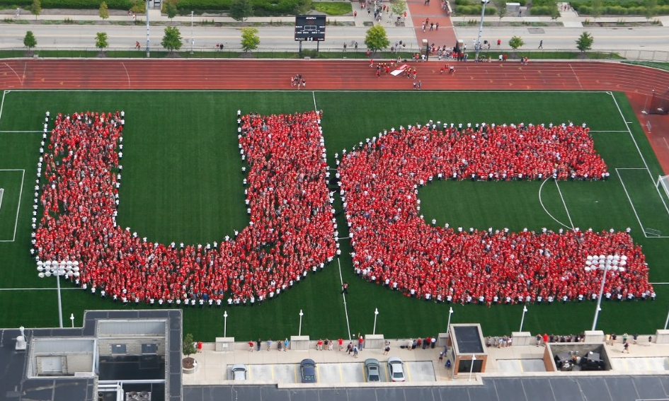Freshman students spell out the letters U C on soccer field.