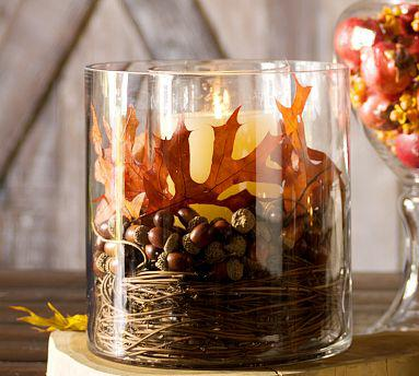 filling a glass candle holder with loose leaves and nuts or pine cones