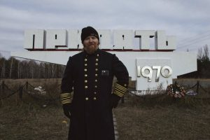 Standing in front of the Pripyat city limits sign. That one button is hard to get in the cold, don't hassle me. (Photo by Robyn von Swank, 2016)