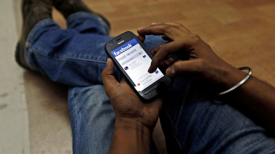 A man surfs the Facebook site on his mobile phone in Mumbai, India, Friday, May 18, 2012 .