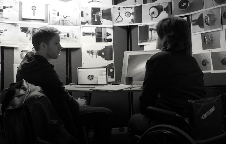 Ryan Eder meets with a consultant, who is in a wheelchair, in his studio