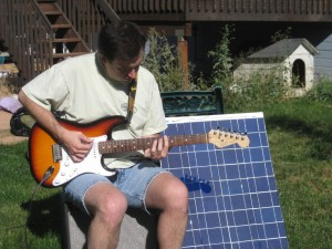 Me playing electric guitar with my amp plugged into the solar panel