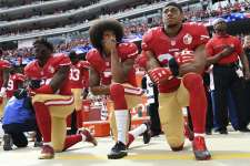 Eli Harold (left), Colin Kaepernick and Eric Reid take a knee during the national anthem before a 2016 game to protest police violence against African Americans, part of a protest that continues this season despite having cost Kaepernick his NFL career.