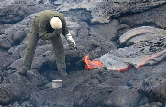 A geologist uses a rock hammer to sample active pahoehoe lava for geochemical analysis on the Kilauea volcano, Hawaii, on June 26, 2009.