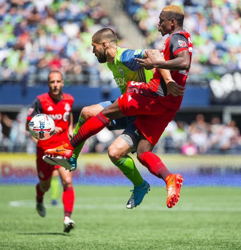 Clint Dempsey and Toronto's Chris Mavinga go after the free ball in the 2nd half.  Toronto FC played the Seattle Sounders in a rematch of last year's MLS Cup Championship Saturday, May 6, 2017 at CenturyLink Field in Seattle.  (Dean Rutz / The Seattle Times)