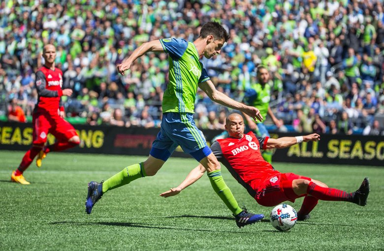 With no other play, Seattle's Alvaro Fernandez punches at the goal, and Toronto's Jason Hernandez makes the tackle, the ball out of bounds to the Sounders in the 2nd half.  Toronto FC played the Seattle Sounders in a rematch of last year's MLS Cup Championship Saturday, May 6, 2017 at CenturyLink Field in Seattle.  (Dean Rutz / The Seattle Times)