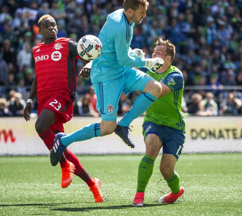 An attempt to get the ball into Jordan Morris at the top of the box is thwarted by Toronto keeper Clint Irwin in the 1st half.  At left is Toronto defender Chris Mavinga.  Toronto FC played the Seattle Sounders in a rematch of last year's MLS Cup Championship Saturday, May 6, 2017 at CenturyLink Field in Seattle.  (Dean Rutz / The Seattle Times)
