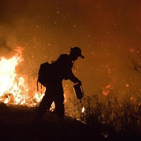 silhouette of a firefighter against fire in the background
