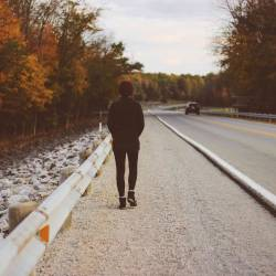 A person walking down a road, alone, facing away.