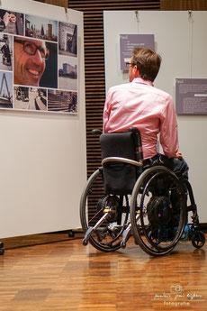 Paul im Rollstuhl vor seiner eigenen Collage in der Ausstellung.