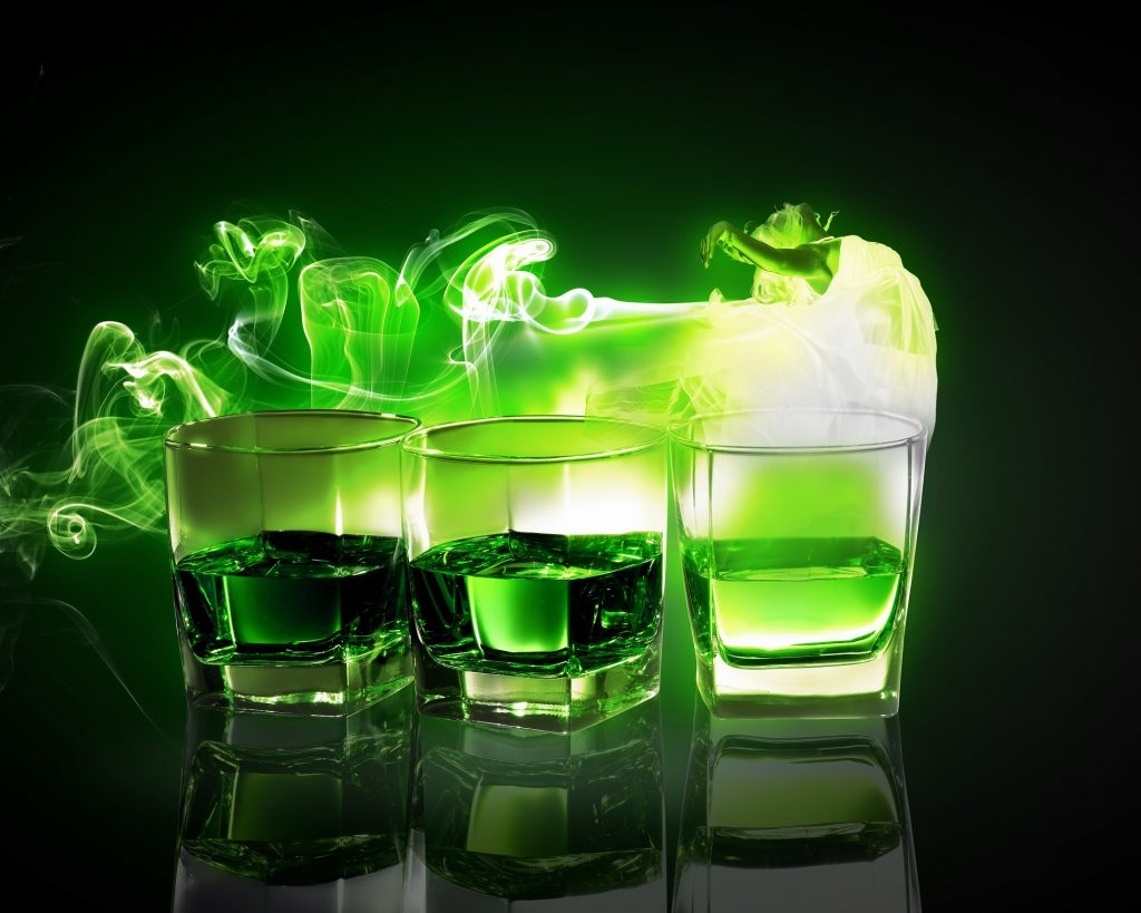 Three glasses of green absinthe with fairy