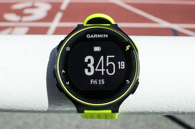 Closeup photo of the face of a black and yellow Garmin Forerunner 230 GPS running watch.
