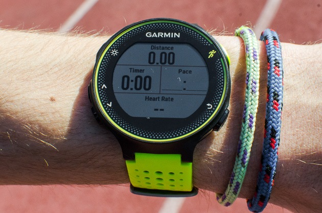 Closeup photo of a person wearing a Garmin Forerunner GPS running watch and two bracelets.
