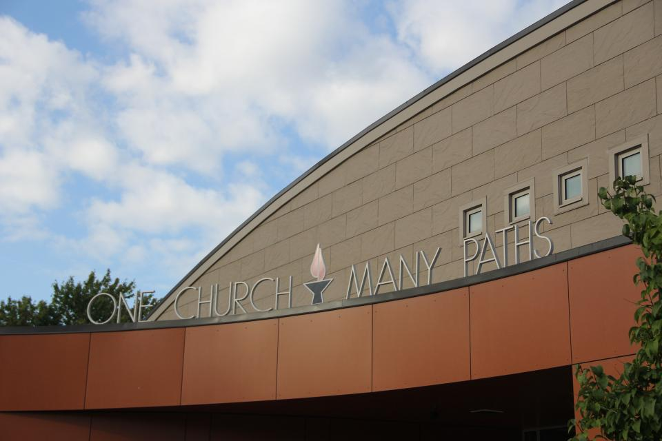 """The outside of a UU congregation's building, reading """"One Church Many Paths"""""""