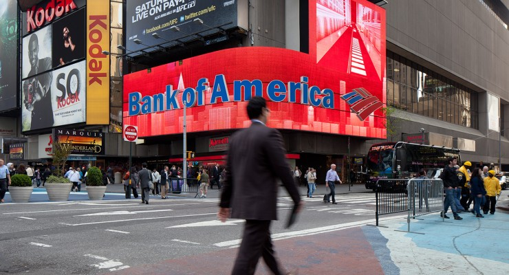 A businessman walks by a large Bank of America digital display in Times Square