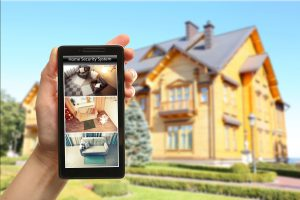 Female hand holding a smartphone on blurred house background. Home security system