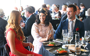 Image of two female and one male racegoer dining and enjoying the atmosphere in one of the dining venues at Flemington Racecourse.