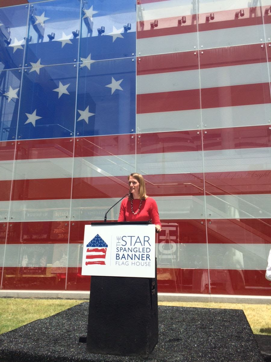 PHoto of Brooke giving a speech in front of a big American flag