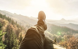 Person relaxing on top of mountain