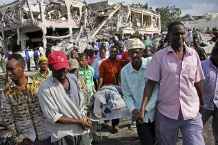 Somalis remove the body of a man killed in Saturday's blast, in Mogadishu, Somalia Sunday, Oct. 15, 2017. The death toll from the huge truck bomb blast in Somalia's capital rose to over 50 Sunday, with more than 60 others injured, as hospitals struggled to cope with the high number of casualties, security and medical sources said. (AP/Farah Abdi Warsameh)