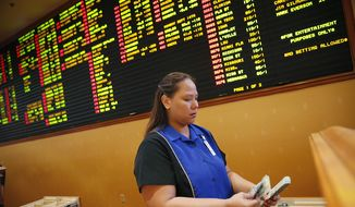 FILE - In this Aug. 20, 2015, file photo, Therese Duenas counts money as she takes bets in the sports book at the South Point hotel and casino in Las Vegas. Las Vegas casinos can't agree on an NCAA tournament favorite, with favorites changing within hours. (AP Photo/John Locher, File) **FILE**