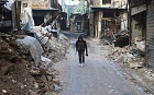 A Free Syrian Army fighter walks with his weapon amid damaged buildings in Old Aleppo