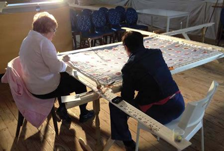 Two women sitting at a table working on a quilt