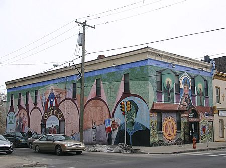 Large mural on two sides of an old two-story corner building