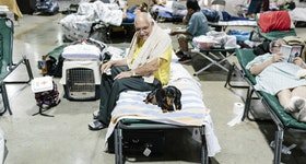 Peter Parkes sat on a cot with his dog, Obama, at an American Red Cross hurricane shelter in Miami.