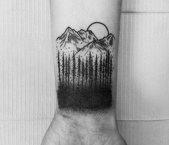 Tattoo on the wrist of the guy the mountains and the woods
