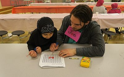 A JFCS volunteer helps Syrian native Aisha complete her homework. (Photo courtesy of JFCS)