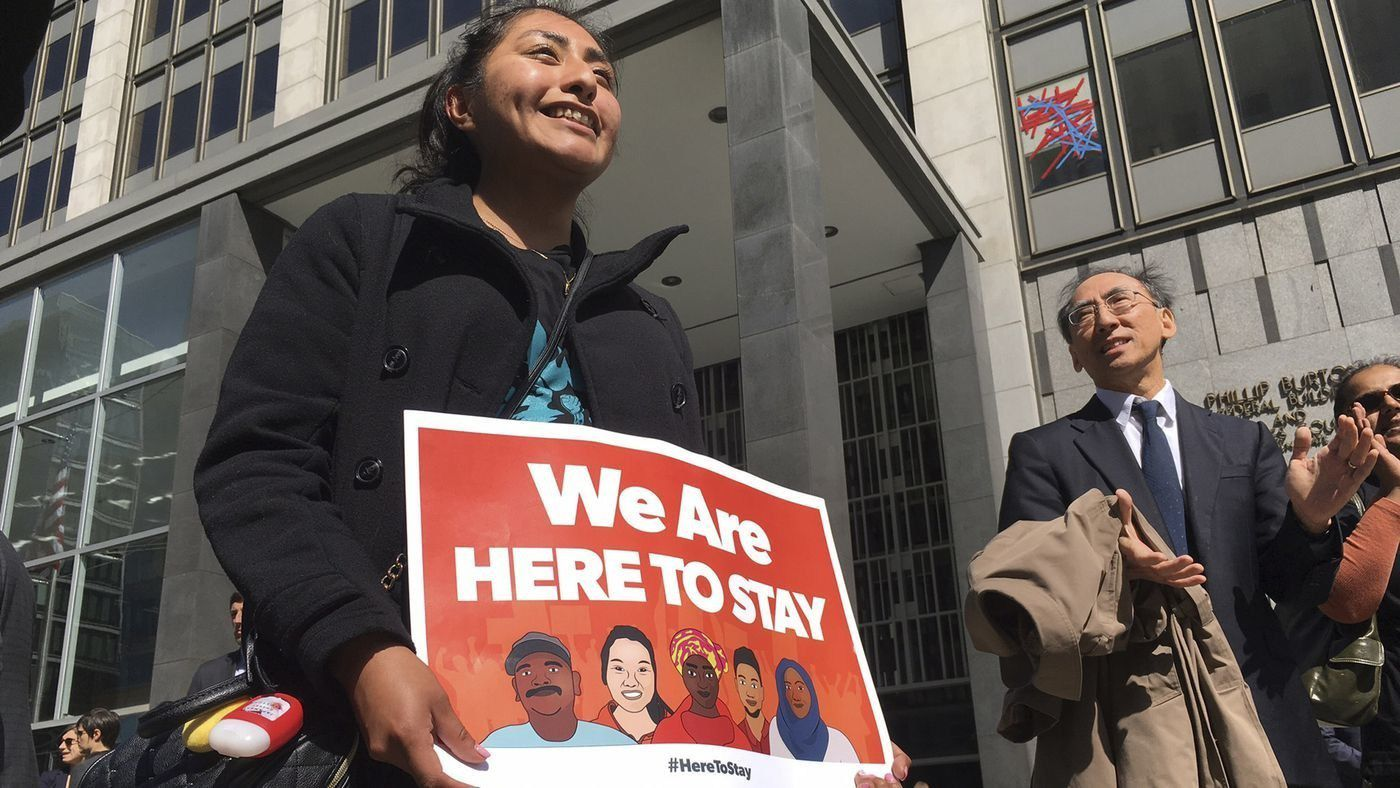 Erica Leyva with the Services, Immigrant Rights and Education Network of San Jose carries a sign outside a courthouse