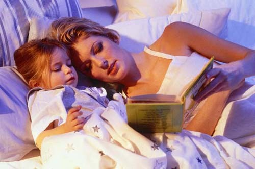 Mother reading out of a book to her daughter --- Image by © G. Baden/zefa/Corbis