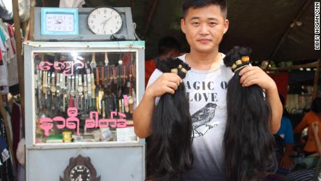 A hair buyer from China holds up bunches of hair he has bought from Yangon's Insein market.