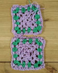 Photograph of Emma's first two crocheted granny squares.