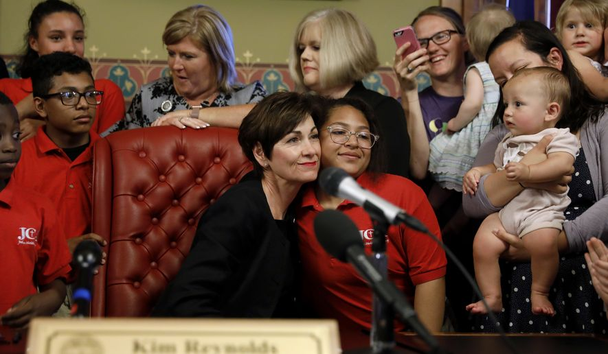 Iowa Gov. Kim Reynolds, left, gets a hug before signing a six-week abortion ban bill into law during a ceremony in her formal office, Friday, May 4, 2018, in Des Moines, Iowa. The bill gives Iowa the strictest abortion restrictions in the nation, setting the state up for a lengthy court challenge. (AP Photo/Charlie Neibergall)