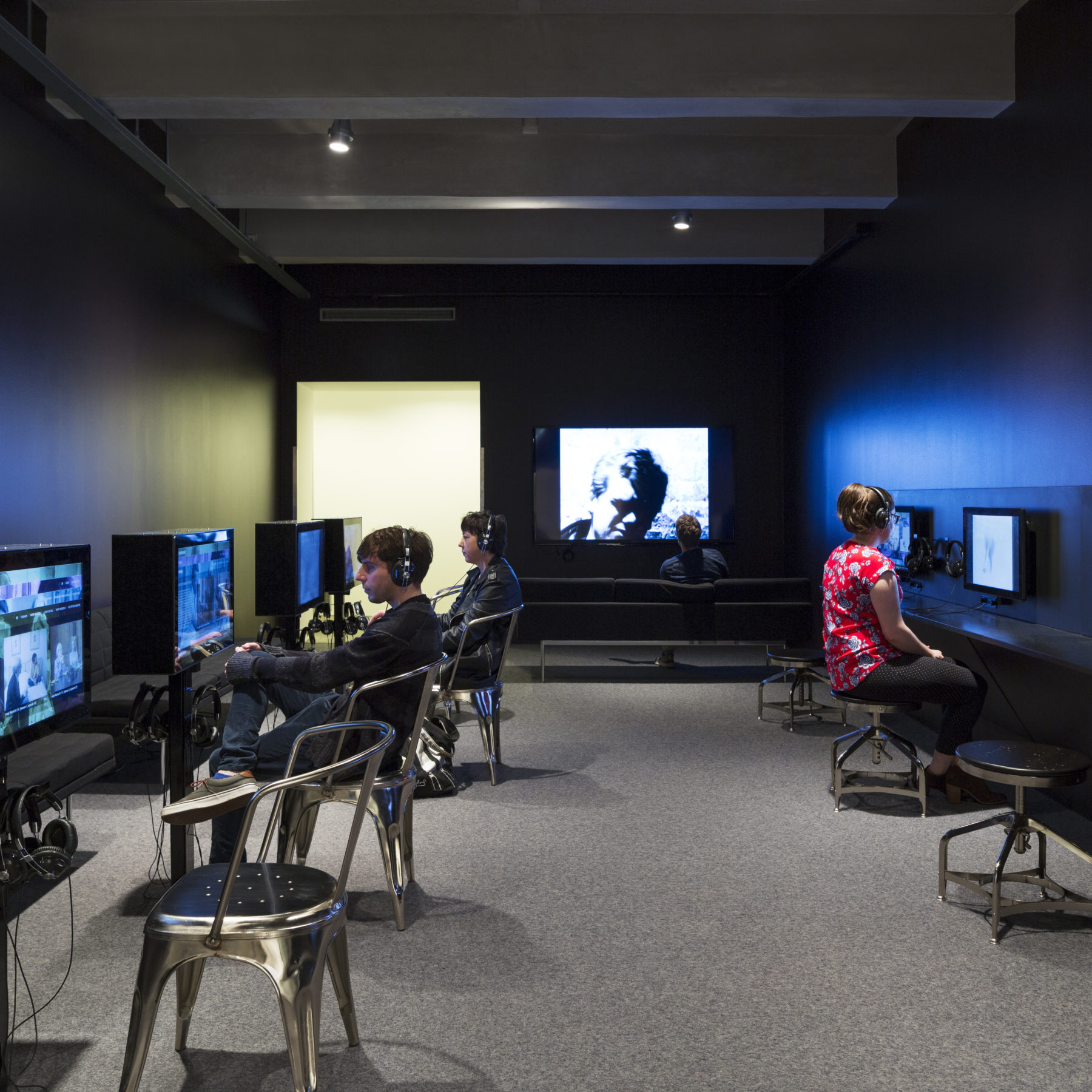 Visitors wearing headphones interact with devices housing Andy Warhol's film and video works lining the walls of a room with black walls. A visitor watches a video that is projected on the back wall of the room.