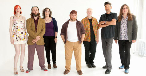 A group of seven people stand in front of a white background looking at the camera. There is one man in the middle of the frame with his hands in his pockets. Three people are standing to his right and three to his left.