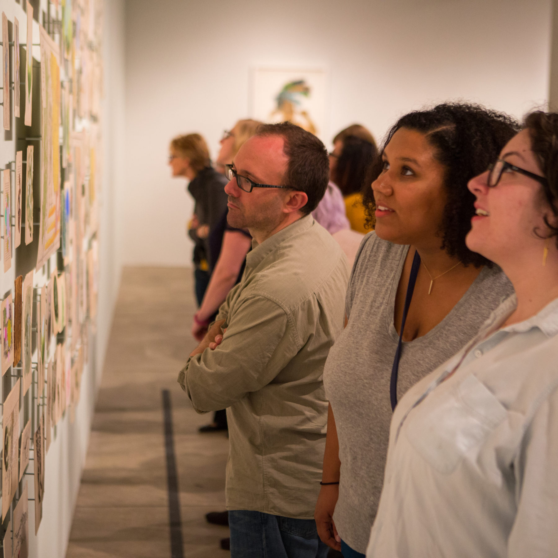 A large group of patrons examines a series of small pieces tacked to the wall on the left side of the image during a Sip and Sketch event.