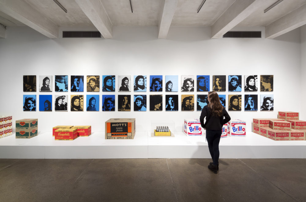 A woman with brown hair dressed entirely in black faces a display of Andy Warhol's works. Two rows of small, screen-printed portraits are hung on a white wall. Some of Warhol's sculptural work-- including reproductions of Campbell's boxes, Brillo boxes, and a tray of silver Coca-Cola bottles-- sit on a low platform in front of the portraits.