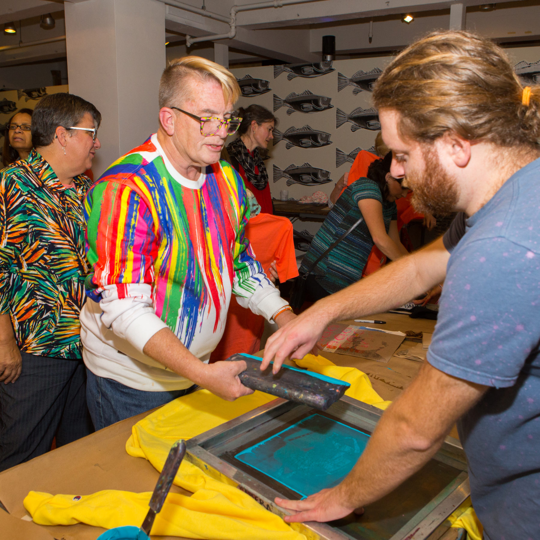 An artist educator helps a teacher wearing glasses and a white sweatshirt with colorful streaks on it screen print a design onto a yellow shirt using turquoise ink.