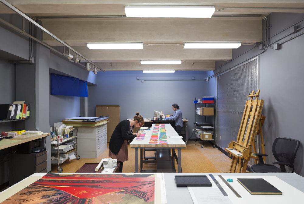 Conservationists work to preserve pieces. A woman in a beige skirt and black cardigan bends over a table in the center of the image, arranging colorful prints. In the backround, a man with curly black hair and a denim shirt works at another table.