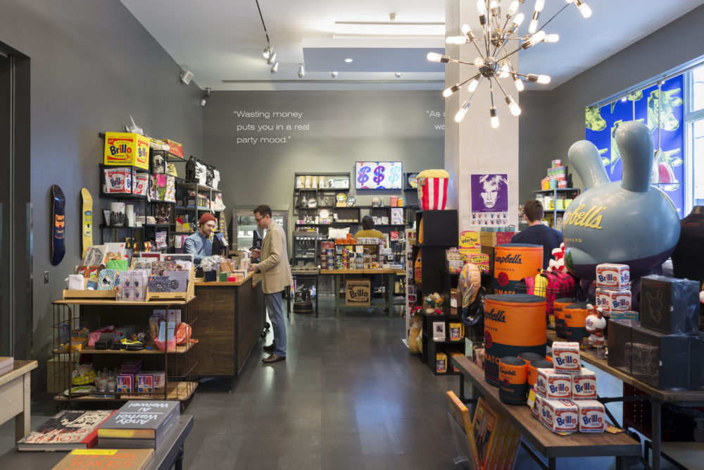 A man in a beige jacket stands at a counter in the Andy Warhol Store. The room is filled with tables and displays featuring books, soup cans, screen prints, and other warhol memorabilia. A quote painted above the shelves on the back wall reads Wasting money puts you in a real party mood.