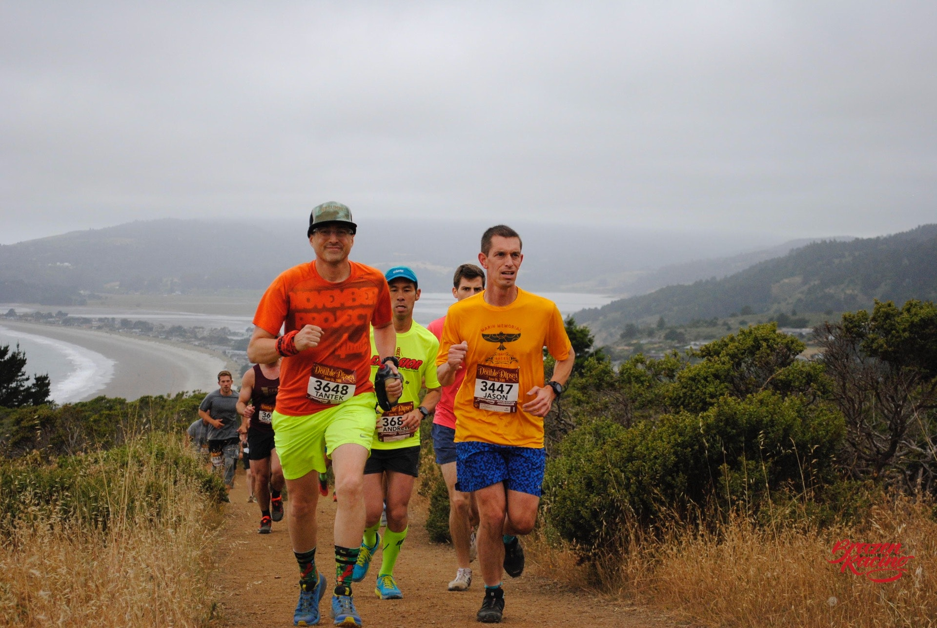 Tantek at the head of a pack of guys running up a trail with Stinson Beach in the distance