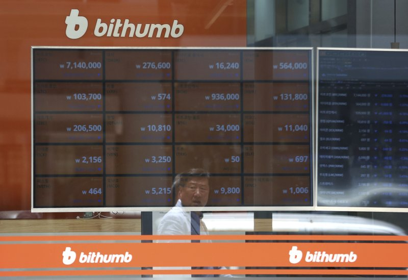 A man is reflected on a screen showing the prices of bitcoin at Bithumb cryptocurrency exchange in Seoul, South Korea, on June 20, 2018.