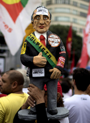 A demonstrator carries a statue in the likeness of Brazil's president Michel Temer during a protest against Brazil's president Michel Temer at Copacabana beach in Rio de Janeiro, Brazil, May 28, 2017. People gathered on Copacabana beach ahead of a concert by Brazilian musical performers calling for new presidential elections while pressure mounts on the country's leader to resign amid corruption allegations. (AP/Leo Correa)