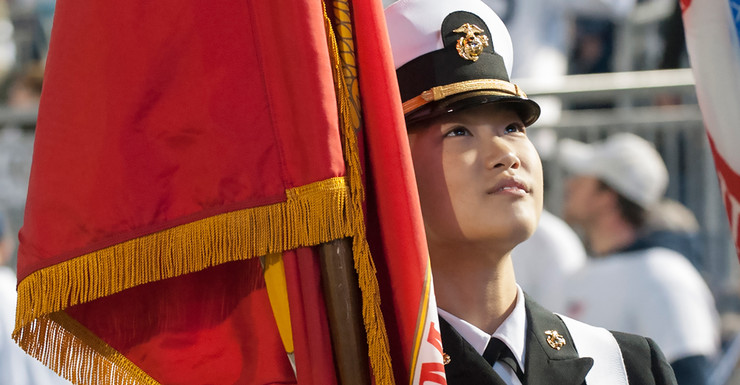 Close up of a student in the navy ROTC color guard with the red flag